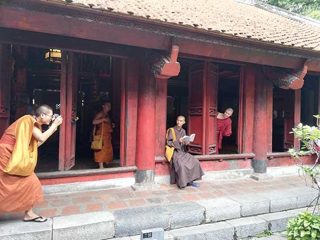 Hanoi. Templo de la literatura. Monges con su atuendo naranja.